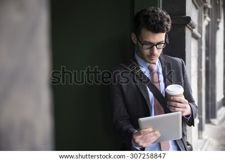Stylish Caucasian man, leaning in a door way and using a Tablet Computer. Outdoors in the city. - stock photo