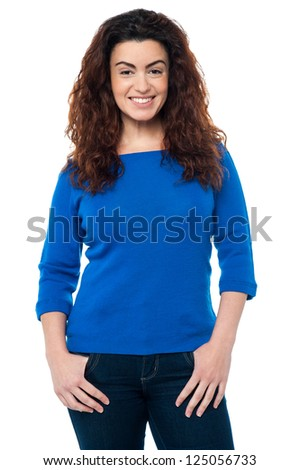 Stylish caucasian woman in casual attire smiling at the camera, long curly hair. - stock photo