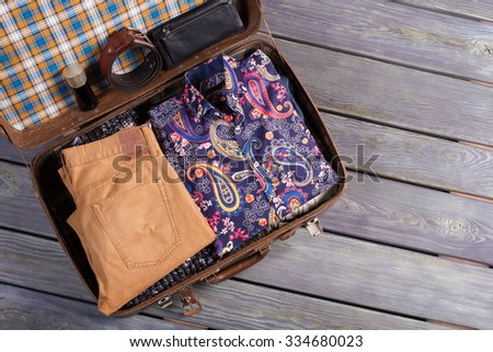 Stylish complex set in a suitcase. Men's clothing in a retro suitcase. Set of traveler. - stock photo