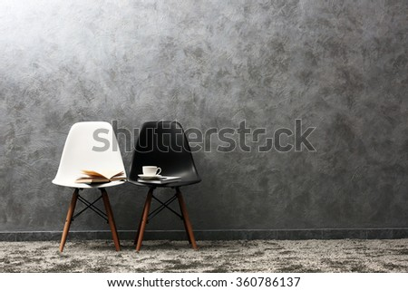 Stylish conception with white and black chairs on grey background - stock photo