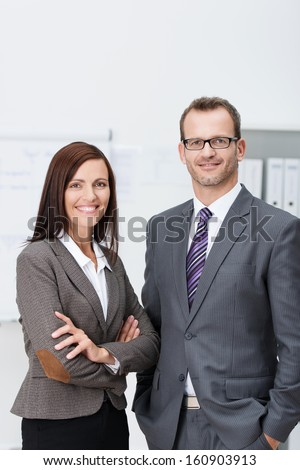Stylish confident business team with an attractive man and woman standing side by side in the office looking at the camera with friendly smiles - stock photo