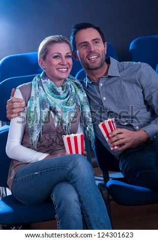 Stylish couple enjoying a movie together sitting in a cinema with their iconic striped containers of popcorn - stock photo