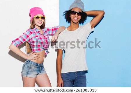 Stylish couple. Funky young couple wearing sunglasses and smiling while standing against colorful background - stock photo