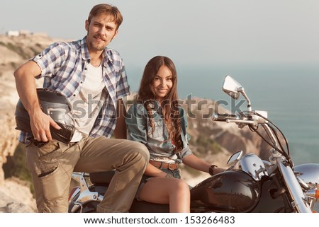 Stylish couple on a motorcycle. He put his foot on the exhaust pipe. She sits behind the wheel. - stock photo