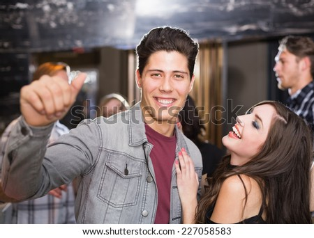 Stylish couple smiling and dancing together at the bar - stock photo