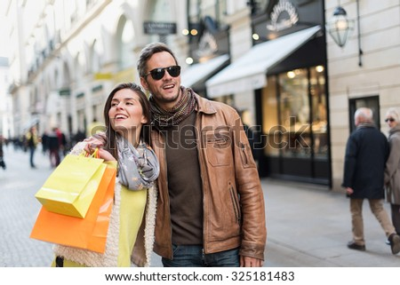 Stylish couple walking in a cobbled car-free street. The grey hair man with beard is wearing sunglasses and a brown leather coat and the woman a yellow top and two shopping bags, they also have scarfs - stock photo