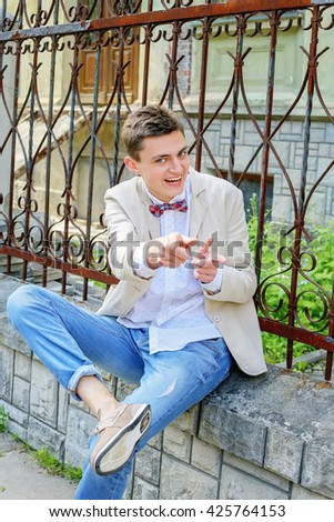 Stylish dandy man in shirt, blue jeans and bowtie sitting near the old metal fence on the city streets. Handsome smiling funny man having fun outdoors. Artistic young guy - stock photo