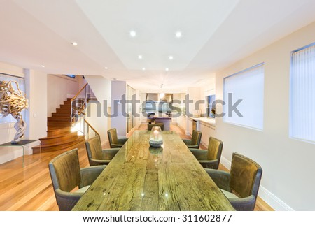 Stylish dining room with long wooden green-coloured table , and comfortable armchairs - stock photo