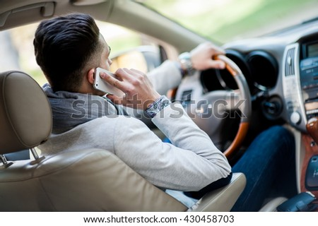 Stylish driver inside his own luxury car. Talk by phone - stock photo
