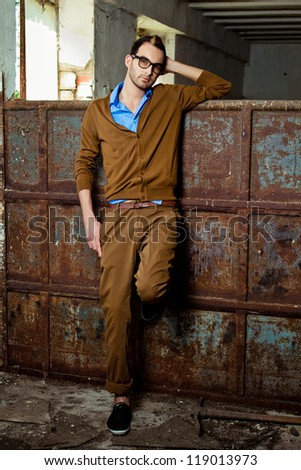 stylish fashionable attractive young man stand grunge rusty metal wall - stock photo