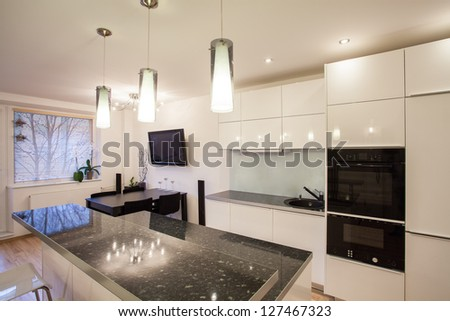 Stylish flat - Bright kitchen with a dark table - stock photo