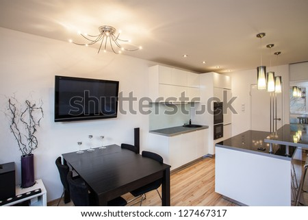 Stylish flat - Dining room and kitchen with tv - stock photo