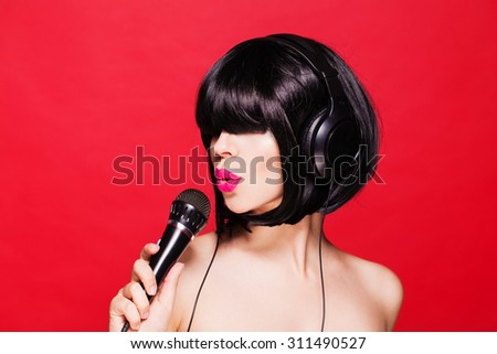 Stylish girl singing with a mike, red background. Karaoke - stock photo