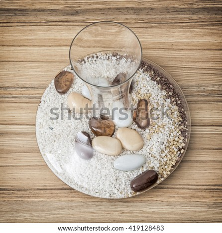 Stylish glass vase full of decorative stones on the wooden background. Indoor decoration. Spa theme. - stock photo