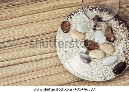 Stylish glass vase full of decorative stones on the wooden background. Indoor decoration. Spa theme. Free place left. Round vase. - stock photo