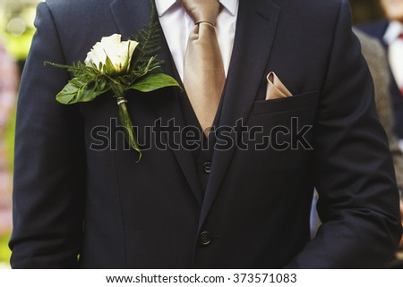 Stylish groom in dark suit with white rose in buttonhole - stock photo
