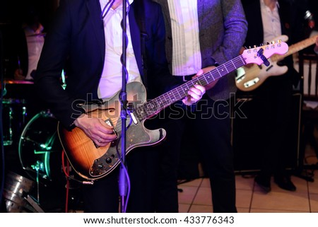 stylish guitarist singer playing on a stage with a band on wedding reception - stock photo