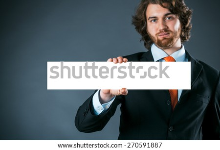 Stylish handsome bearded young businessman holding a rectangular blank sign or banner in his hand with copyspace for your text or advertising over a grey background - stock photo