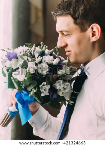 Stylish handsome dark haired groom sniffing a wedding bouquet standing near the window - stock photo
