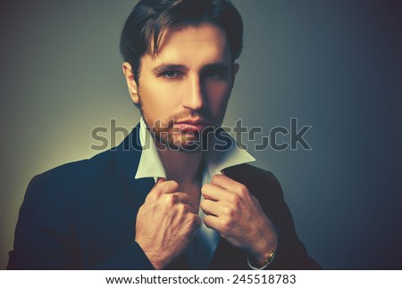 stylish handsome man in a suit in dark colors - stock photo
