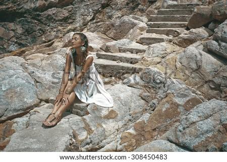 stylish hippie girl sitting on stone staircase - stock photo