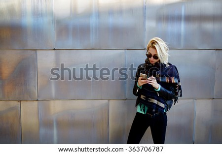 Stylish hipster girl chatting on cell telephone while standing against urban metallic background with copy space area for your text message or advertising content,young female using mobile smart phone - stock photo