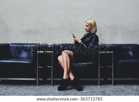 Stylish hipster girl chatting on mobile smart phone with her friend which she awaits before a photo session in the fashion studio, young blonde woman reviewing traffic in Internet via cell telephone  - stock photo