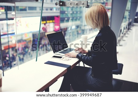 Stylish hipster girl is using for remote freelance job portable net-book during her vacation in China.Female student is searching information in internet via laptop computer during rest after shopping - stock photo
