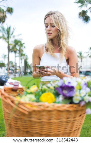 Stylish hipster girl reading text message on a telephone while ride on her retro bicycle with a basket of flowers in the park, gorgeous female enjoying recreation time while chatting on mobile phone - stock photo