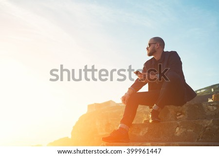 Stylish hipster guy wearing fashionable sunglasses and clothes is listening to music in social network via cellphone, while is sitting on a rock against sky with sun rays. Copy space area background - stock photo