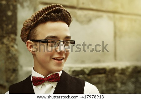 stylish hipster man smiling with confidence, funny emotions on background of old city street wall - stock photo