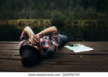 stylish hipster traveler playing harmonica at sunny lake in the forest in mountains - stock photo