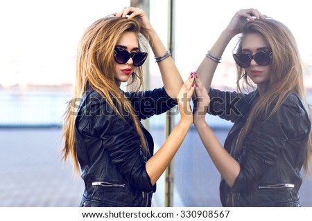 Stylish lady in black, posing outdoor, glamour sexy total black look, leather biker jacket, nice autumn day, luxury grunge style, posing near mirrored wall. - stock photo