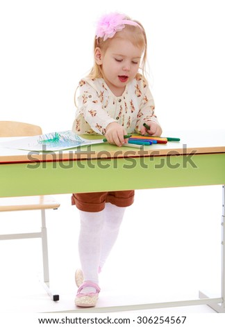 Stylish little blonde girl with a pink bow on his head draws with markers on a piece of paper while standing at the table. The girl is dressed in a white blouse and brown shorts-Isolated on white - stock photo