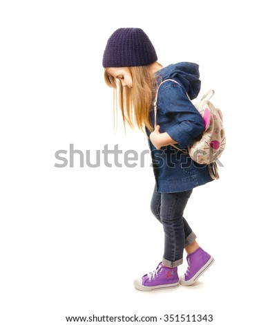 Stylish little girl in denim clothing, sneakers and backpack standing on a white background - stock photo
