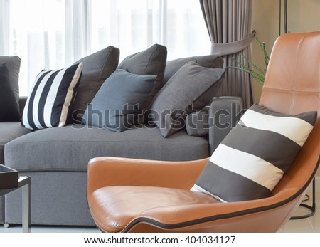 stylish living room design with grey and black striped pillows on comfortable sofa - stock photo