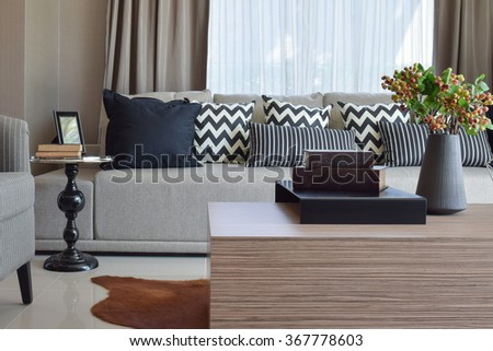 stylish living room design with grey striped pillows on comfortable sofa - stock photo