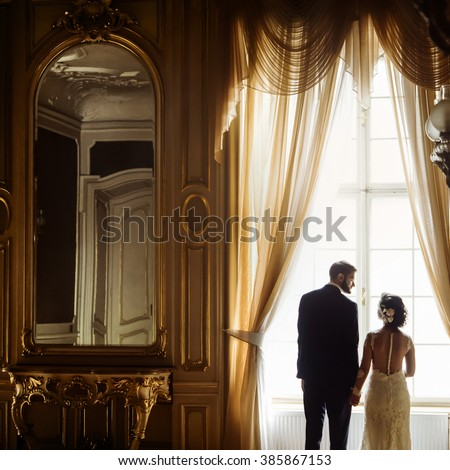 stylish luxury bride and handsome elegant groom holding hands at gorgeous window on the background of rich interior in old building - stock photo