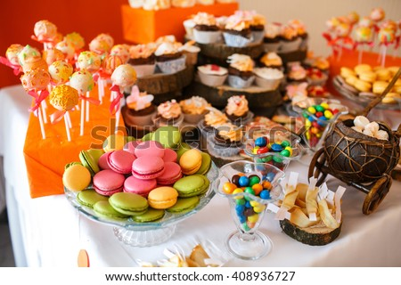 stylish luxury decorated orange candy bar for the celebration of a wedding of happy couple, cathering in the restaurant - stock photo