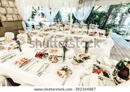 stylish luxury decorated table with flowers and delicious food, celebration wedding, catering in the restaurant - stock photo