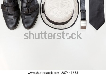 Stylish man accessories. Black leather shoes, belt  , isolated on white wooden table. Top view. - stock photo