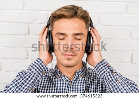 stylish man listening to music on headphones - stock photo