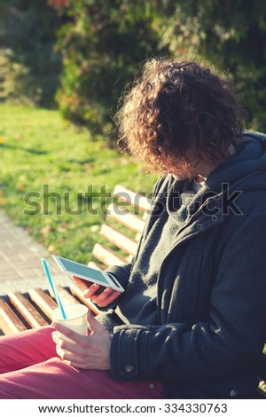 Stylish man sitting in autumn park on a bench, reading the electronic book and drink some coffee, outdoor relax. - stock photo
