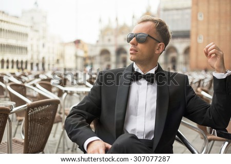Stylish man sitting in cafe in tuxedo - stock photo