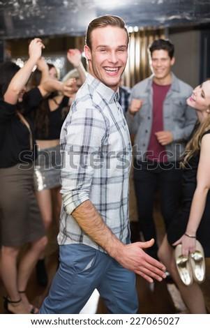 Stylish man smiling on the dancefloor at the bar - stock photo