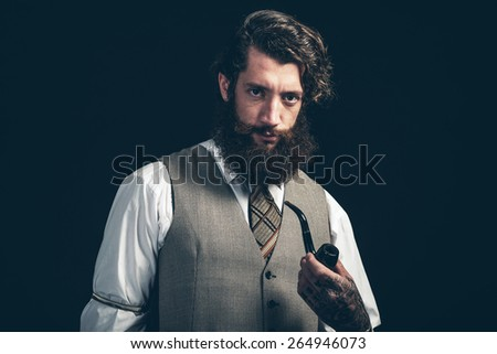 Stylish man with a bushy beard in retro fashion standing smoking a pipe looking at the camera with a serious expression - stock photo