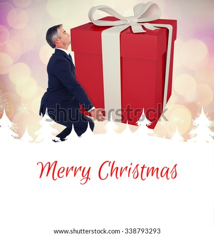 Stylish man with giant gift against glowing christmas background - stock photo