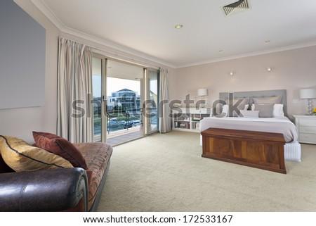 stylish master bedroom with balcony in australian mansion - stock photo