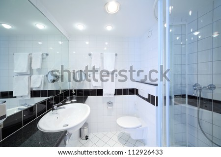 Stylish modern bathroom with shower, sink, toilet and white tile. - stock photo
