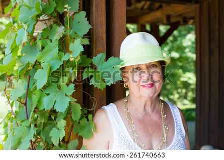 Stylish modern senior lady in a trendy hat standing alongside a climbing green grape vine smiling at the camera, head and shoulders portrait - stock photo